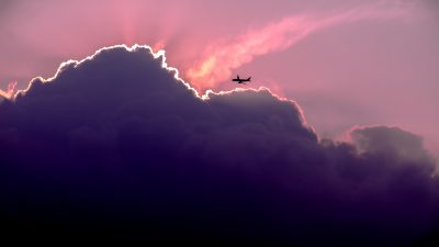 picture of distant airplane flying over clouds at sunset by aviation accident attorney